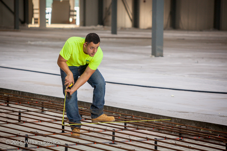 Measuring rebar for concrete pour by Psolka Photography