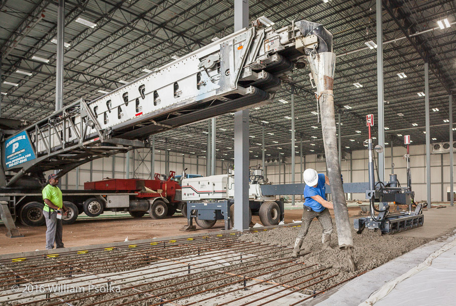 Concrete being delivered and poured via conveyor belt by Psolka Photography